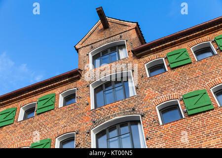 Old house facade, red brick wall with windows and crane beam. Copenhagen, Denmark - Stock Photo