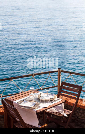 Wooden table with white, dishwater and chairs on ocean in a restaurant in Italy, Europe - Stock Photo