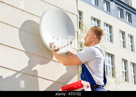 Man Fitting TV Satellite Dish - Stock Photo