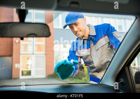 Man Cleaning Car Window With Cloth - Stock Photo