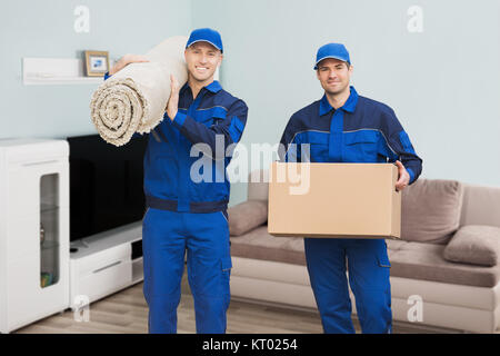 Two Male Movers Standing In House - Stock Photo