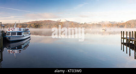 Mist rises from the calm waters of Windermere lake at Ambleside Pier, where a ferry boat is moored, under thew snow - Stock Photo