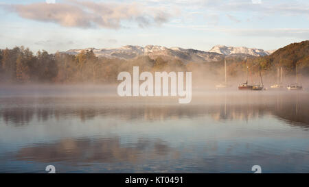 Mist rises around boats moored on Windermere lake, beside woodland trees in autumn colours, at Ambleside in England's - Stock Photo