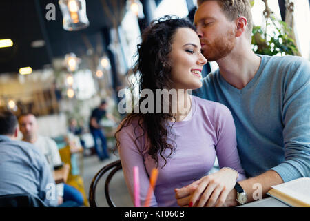 Young happy couple on date in coffee shop - Stock Photo