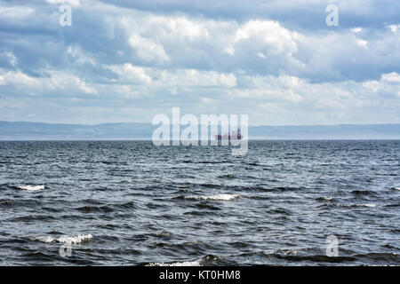 Cargo ship on the horizon in Kirkcaldy, Scotland - Stock Photo