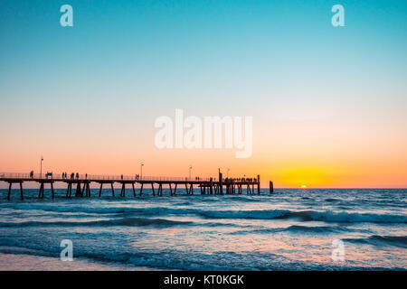 Beautiful warm sunset with people on the jetty at Glenelg beach, South Australia - Stock Photo