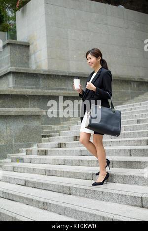 Businesswoman leaving office - Stock Photo