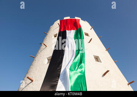 Old tower in Abu Dhabi decorated with huge UAE flag for the celebration of 45th National Day - Stock Photo