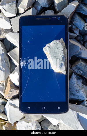 Frustrated phone on the rocks. Glass shattered on rocks on a sma - Stock Photo
