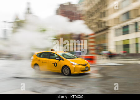 A panning shot of a yellow taxi cab driving along a street in lower Manhattan, New York, USA - Stock Photo