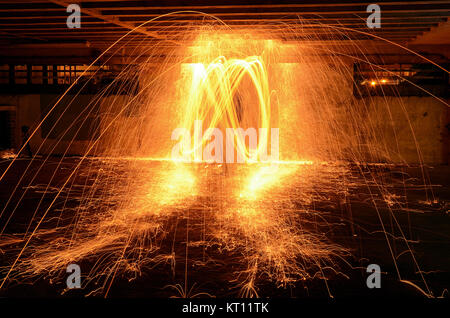 Wire wool spinning with fire in underground car park. Flame, fire, sparks. - Stock Photo