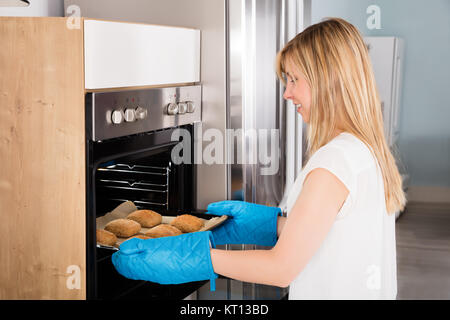 Woman Taking Baking Tray Out From Oven - Stock Photo
