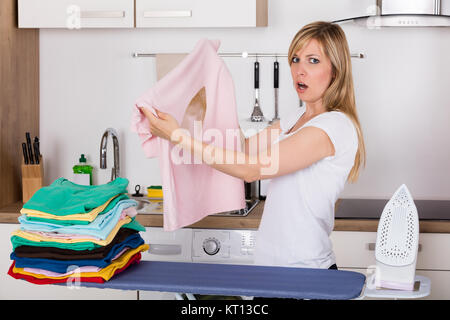 Shocked Woman Looking At Burnt T-shirt - Stock Photo
