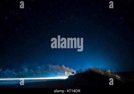 strange silhouette in a dark spooky forest at night, mystical landscape surreal lights with creepy man - Stock Photo
