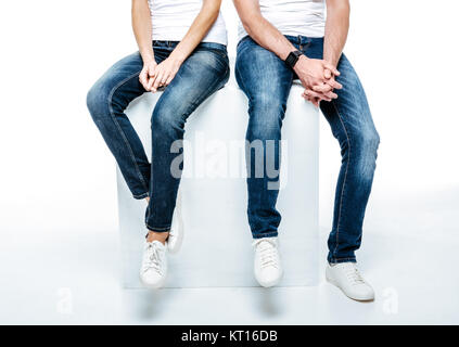 Couple sitting in jeans and white shoes - Stock Photo
