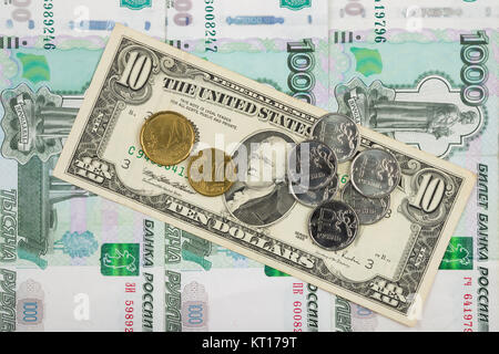Coins ruble and the euro are on the bill of ten dollars which lies on a pile of thousand-Russian banknotes - Stock Photo