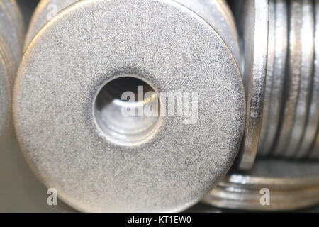 Metal washers macro selective focus - some face on and others from side view - background - Stock Photo
