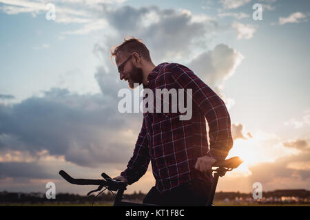 35 year old hipster male with his bike at Templehof Field in Berlin, Germany enjoying a beautiful sunset. - Stock Photo