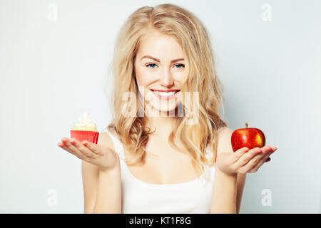 Smiling Woman with Healthy and Unhealthy Food. Difficult choice. Overweight Concept - Stock Photo
