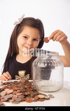 Seven year old girl holding coin with her savings jar on the desk - Stock Photo