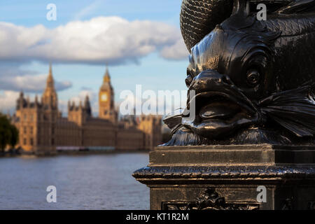 Close up of the distinctive fish design on the cast-iron lamp posts in Westminster, London with the Houses of Parliament - Stock Photo