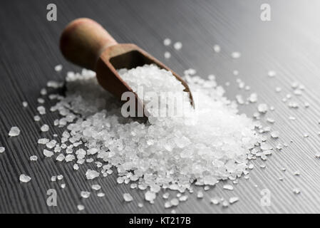 wooden scoop with coarse salt on black table - Stock Photo