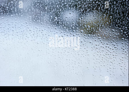 Water droplets running down a glass window on a snowy day - Stock Photo