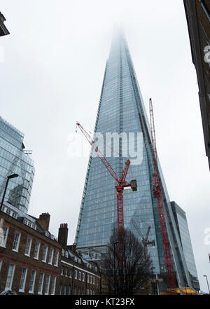 The Shard Skyscraper with its Top in Cloud and a Red Industrial Crane on a Cold Winter Day in December London England - Stock Photo