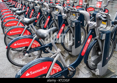 Lines of Red Rental Bicycles with Snow on Saddles Sponsored by Santander near Tower Bridge London England United - Stock Photo