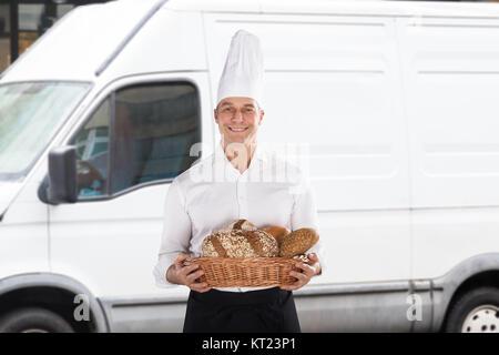 Baker Holding A Basket Full Of Bread Loaf - Stock Photo