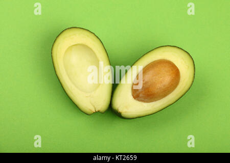 Two halves of fresh cut avocado on green paper - Stock Photo