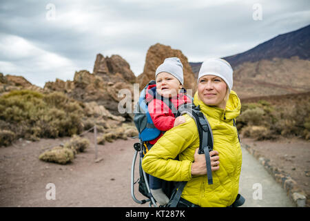 Super mom with baby boy travelling in backpack. Mother on hiking adventure with child, family trip in mountains. - Stock Photo