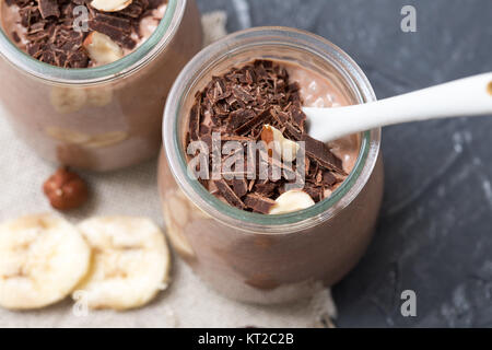 Chocolate pudding with chia seed, bananas and nuts, in a glass jar - Stock Photo