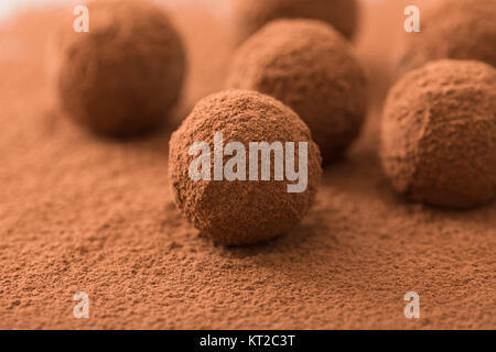 Close up of group of appetizing black chocolate truffles covered in cocoa dust. Shallow depth of field. - Stock Photo