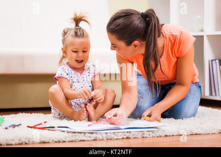 Mother and daughter in their home. They are looking at coloring book. - Stock Photo