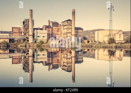Old Factory. Chemical plant. Pipes,smokestacks,storage tank and electric pylon. Reflected in the river.Photo in - Stock Photo