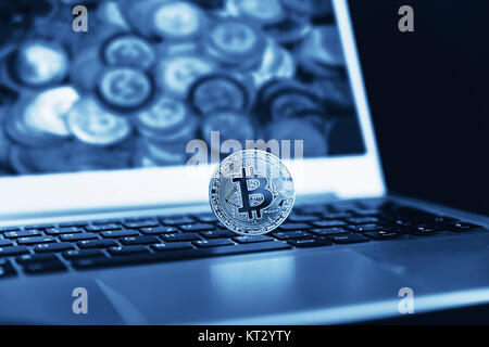 Blue close up golden bitcoin coin crypto Currency background concept. Golden bitcoin coin on the black laptop keyboard. - Stock Photo