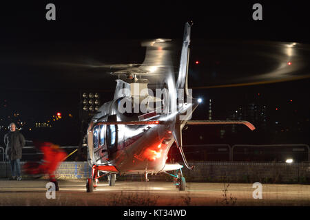 Helicopter being used as a prop on a film set during a night time film shoot taking place on Albert Island in London's - Stock Photo