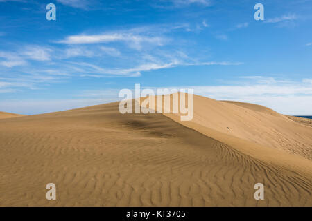 Sand in the Dunes of Maspalomas, a small desert on Gran Canaria, Spain. Sand blowing in the wind on top of the hill. - Stock Photo