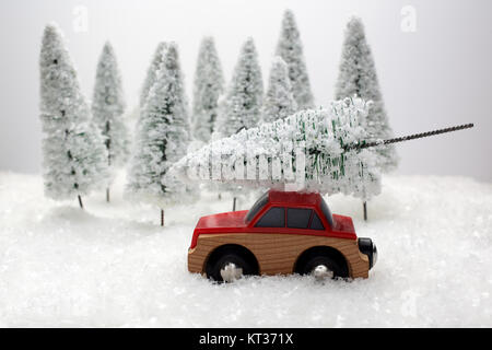 Red car carrying a Christmas tree in a snow covered miniature evergreen forest - Stock Photo