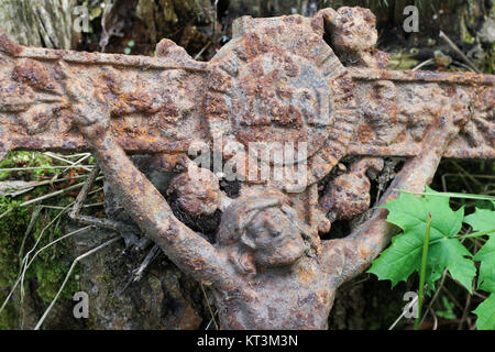 Old rusty cross with Jesus lost in the woods - Stock Photo