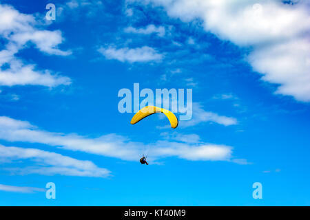 Paraglider flying alone with blue sky in the background - Stock Photo