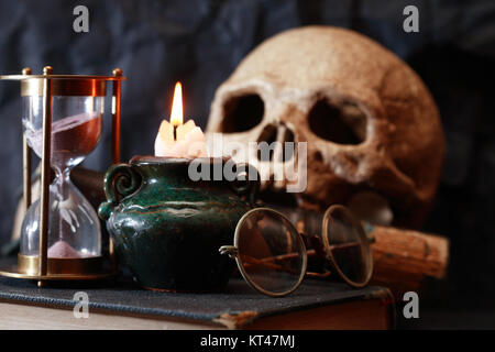 Vintage still life with lighting candle near hourglass and skull - Stock Photo