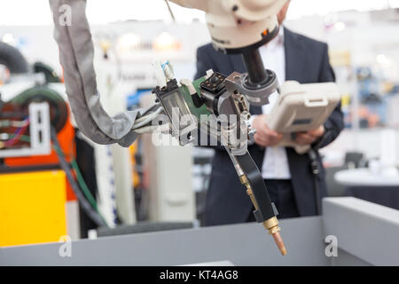 Industrial welding robotic arm, blurred operator in the background - Stock Photo