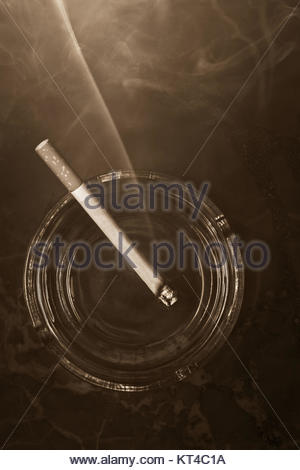 A lit cigarette rests in a glass ashtray, in a smokey atmosphere, on a marble background. Concept: habits, addiction, - Stock Photo