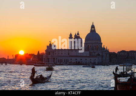 Colourful orange sunset over the Venice lagoon and Basilica di Santa Maria della Salute with  gondolas with tourists - Stock Photo