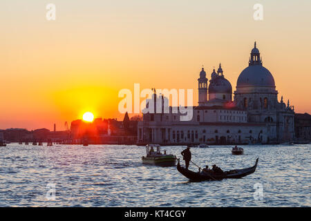 Colourful orange sunset over the Venice lagoon and Basilica di Santa Maria della Salute with boats and a gondola - Stock Photo