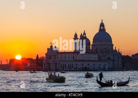 Colourful orange sunset over the Venice lagoon and Basilica di Santa Maria della Salute with boats and a gondola - Stock Photo