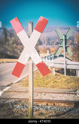 Diagonal cross sign in front of rails - Stock Photo