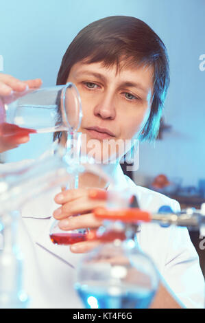 Portrait of a female scientist in white coat working in a chemical laboratory - Stock Photo